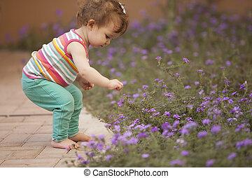 Cute baby girl picking flowers