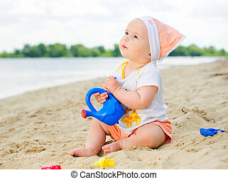 baby girl playing on the beach with sand.