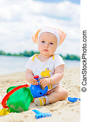 cute baby girl playing on the beach with sand.