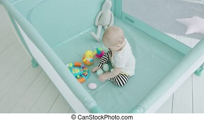 Cute baby girl playing toys in playpen at home