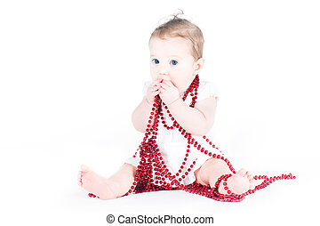 Cute baby girl playing with red necklace