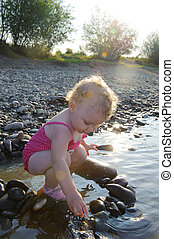 Cute baby girl playing with stones