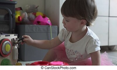 Cute baby girl playing with toy at home