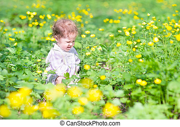 Cute baby girl playing with yellow flowers