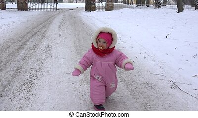 cute baby girl quickly walk on snowy path in winter time. 4K