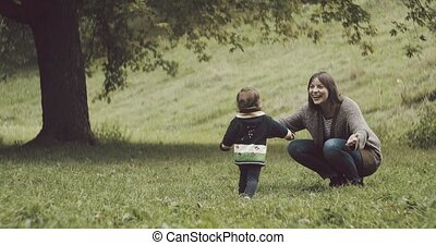 Cute baby girl running to her mother for a hug.