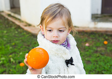 Cute baby girl showing orange