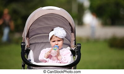 Cute baby-girl sitting in the carriage and drinking milk in...