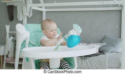Cute baby girl sitting on highchair licking plate