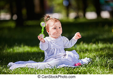 Cute baby girl sitting on the green grass in the city park at warm summer day.