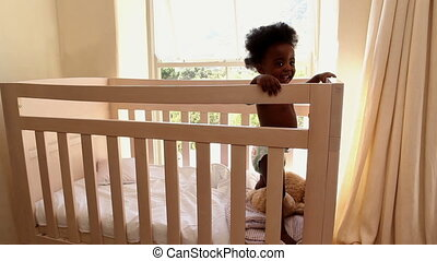 Cute baby girl standing in her crib looking at camera at...
