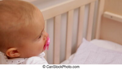 Cute baby girl standing up in her crib