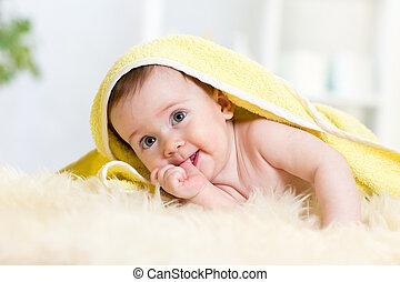 Cute baby girl sucking her thumb. Child lying under towel.