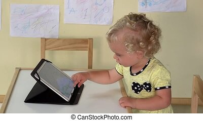cute baby girl using tablet computer sitting near small table.