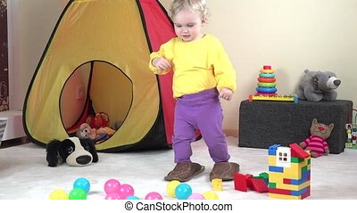 Cute baby girl walk with big father slipper between toys at home.