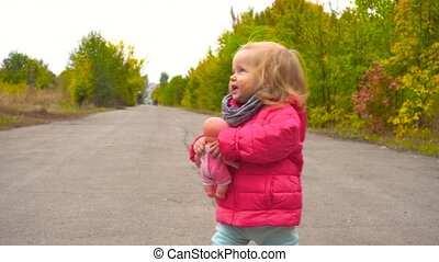Cute baby girl walkin in autumn park with doll