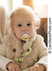 Cute baby girl with a pacifier in her mouth