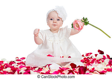 cute baby girl with flower sitting among rose petals