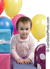 Cute baby girl with gifts and balloons