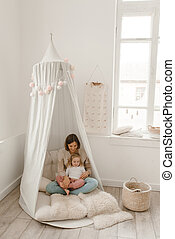 Cute baby girl with her mom play in a minimalistic children's room.