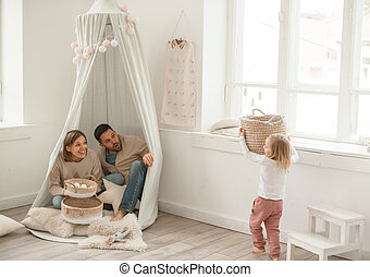 Cute baby girl with her parents play in a minimalistic children's room.