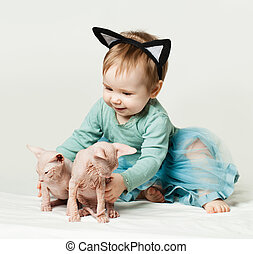 Cute baby girl with kittens at home