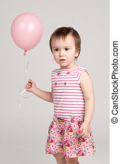 Cute baby girl with pink balloon