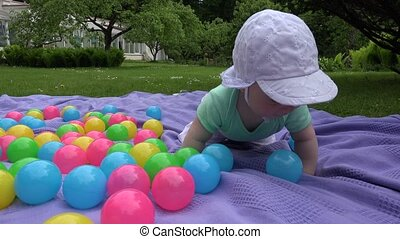 Cute baby girl with white hat crawl between colorful balls...