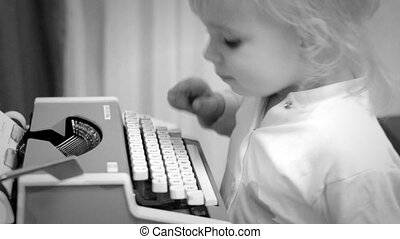 Cute Baby Girl Writing a Book on a Vintage Typewriter, Black and White
