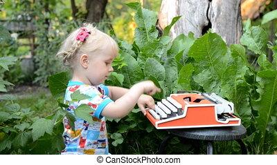 Cute Baby Girl Writing on a Vintage Typewriter Machine