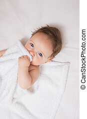 Cute baby holding blanket in crib - High angle portrait of ...