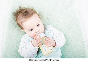 Cute baby in a green sweater drinking milk from a bottle