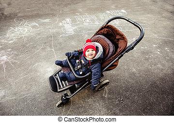 Cute baby in stroller on street