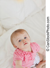Cute baby looking at the camera while sitting on a bed