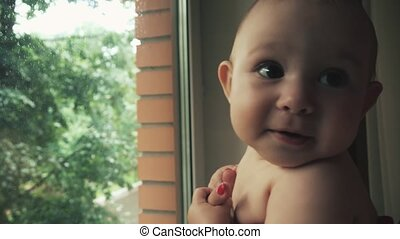 Cute baby looking at the rain behind window