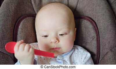 Cute Baby Lying in Pram Eating a Red Spoon - Adorable cute...