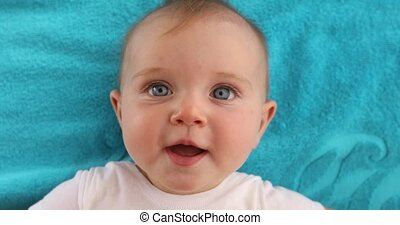 Cute baby lying on towel - Adorable blue eyed baby with...