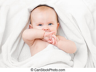 Cute baby lying on white towel and sucking own hand