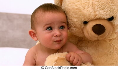 Cute baby on a bed with teddy bear