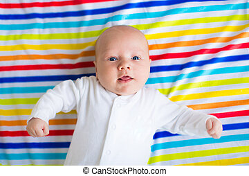 Cute baby on a colorful blanket - Newborn baby boy in bed....