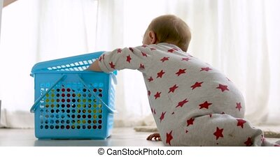 Cute baby opening toy box - Cute baby in crawl suit opening...