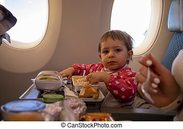 cute baby passenger eats in aircraft special meal. infant young traveler