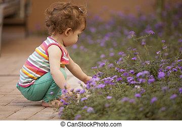Cute baby picking flowers
