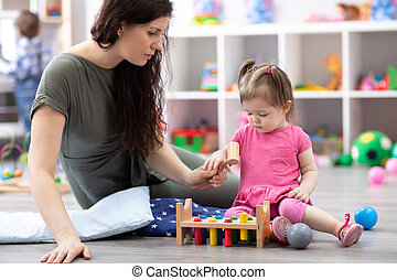 cute baby play with carer or babysitter in nursery or kindergarten