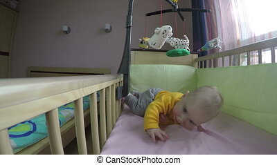 cute baby play with carousel in bed and roll over on belly. 4K