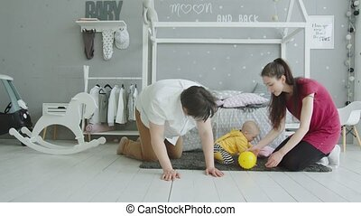 Cute baby playing ball crawling with parents at home