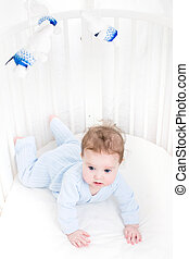 Cute baby playing in a white round crib