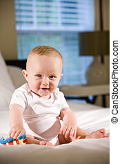Cute six month old baby playing with a toy sitting on bed