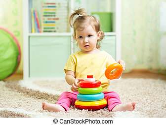 cute baby playing with colorful toy at home