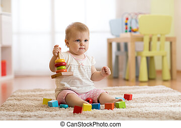 Cute baby playing with colorful toys sitting on carpet in white sunny bedroom. Child with educational toys. Early development.